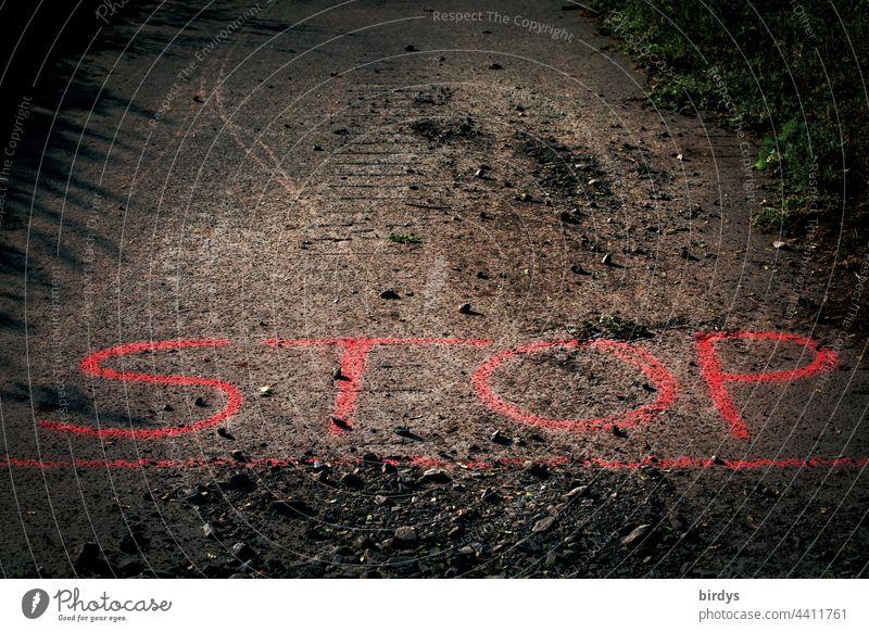 Stop. Rote Linie, Schrift auf einer asphaltierten Straße, Schottersteine liegen auf dem Straßenbelag rot rote Linie gesperrt Sicherheit Schriftzeichen Befehl