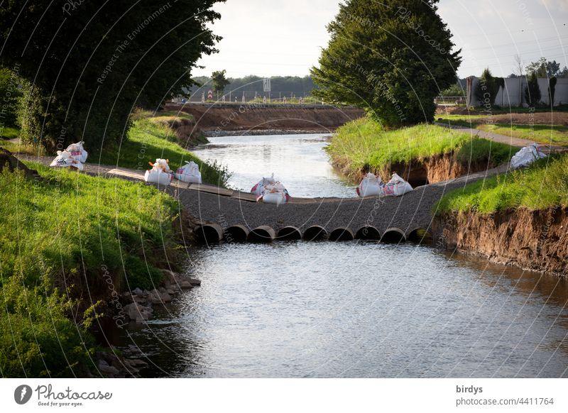 Nach der Flutkatastrophe in Erftstadt-Blessem errichtete Behelfsbrücke, im Hintergrund die unterspülte Autobahn A61 mit eingestürzten Lärmschutzwänden