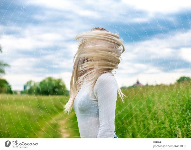 junge Frau mit zerzausten Haaren glücklich wehen Wind sinnlich windig anmutig hübsch single fröhlich Porträt attraktiv optimistisch entspannt blond Freude