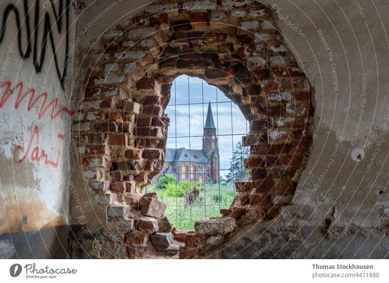 Kirche in Manheim, einem Dorf, das für den Braunkohletagebau abgerissen wird, Blick durch ein Loch in einer Backsteinmauer Verlassen Architektur