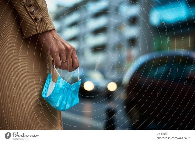 Frau hält Schutzmaske in den Händen auf einer Straße in der Stadt Großstadt Mundschutz schützend Spaziergang Coronavirus Sperrung Quarantäne Business Mantel