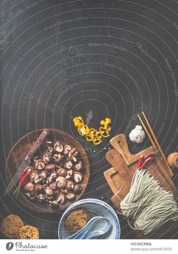Leckere Zutaten der asiatischen Küche frisch zubereitete hausgemachte Nudeln auf Schneidebrett und Holzteller mit Shiitake-Pilzen, Chilischoten, traditionelle Suppenschalen auf dunklem Hintergrund. Rahmen.