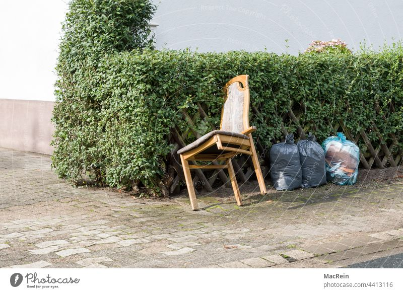 Sperrmüll am Strassenrand aussenaufnahme abfall bürgersteig entsorgen farbfoto hecke holzstuhl kaputt niemand sperrmüll strassenrand stuhlbein zaun