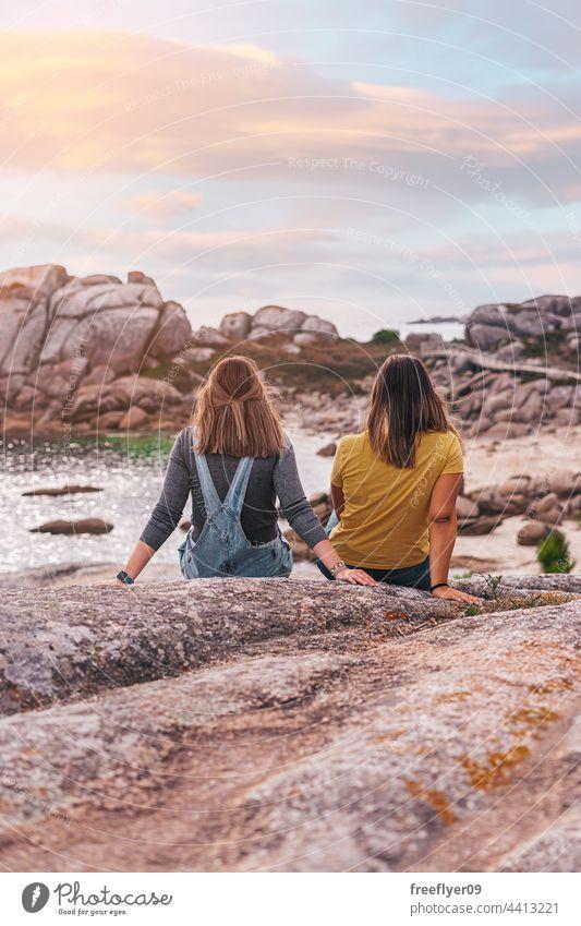 Zwei Freundinnen, die das Meer betrachten Frau Freunde Textfreiraum Kontemplation betrachtend Sonnenuntergang Meeresufer Steine Küstenlinie mediterran Kaukasier