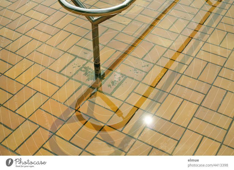 Teilansicht eines beigefarben gefliesten Kneippbeckens mit Metallhandlauf im Sonnenschein / Wassertreten Handlauf kneippen Stoffwechselanregung gesund