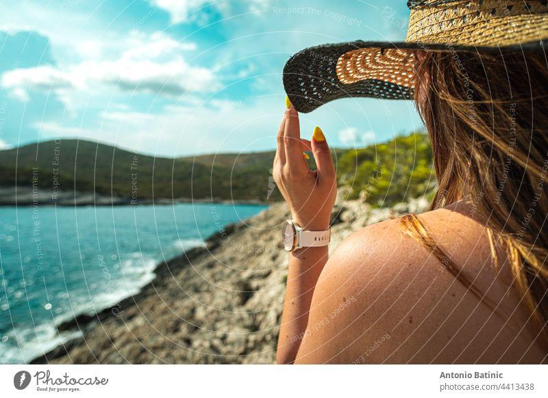 Seitenansicht eines nicht wiederzuerkennenden brünetten Mädchens, das sich im Sommer an ihrem Heuhut festhält. Stehend in der Nähe der Küste des adriatischen Meeres, Konzepte von Reisen, Sommer und Urlaub