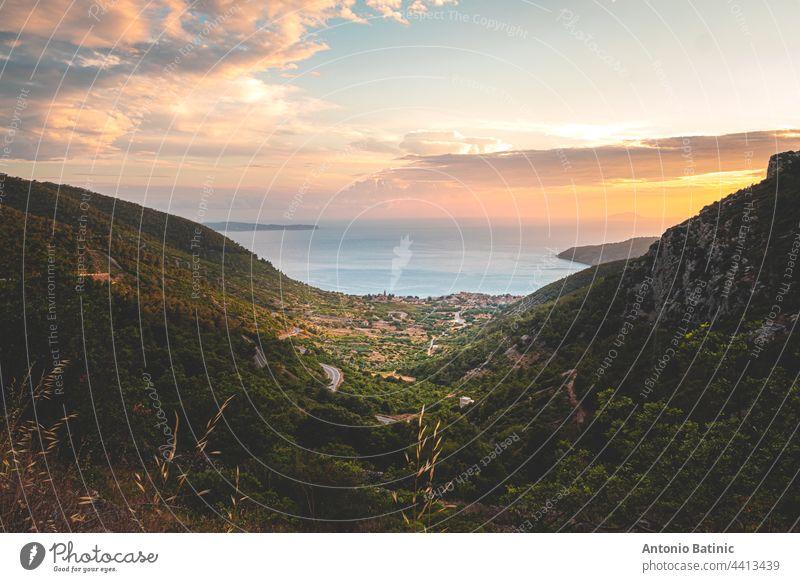 Fantastischer Sonnenuntergang auf der Insel Vis in Kroatien. Komiza Stadt in der Ferne. Goldene Stunde, orangefarbener Himmel und die wunderschöne blaue Adria. Grüne Berge umgeben die kleine malerische Stadt