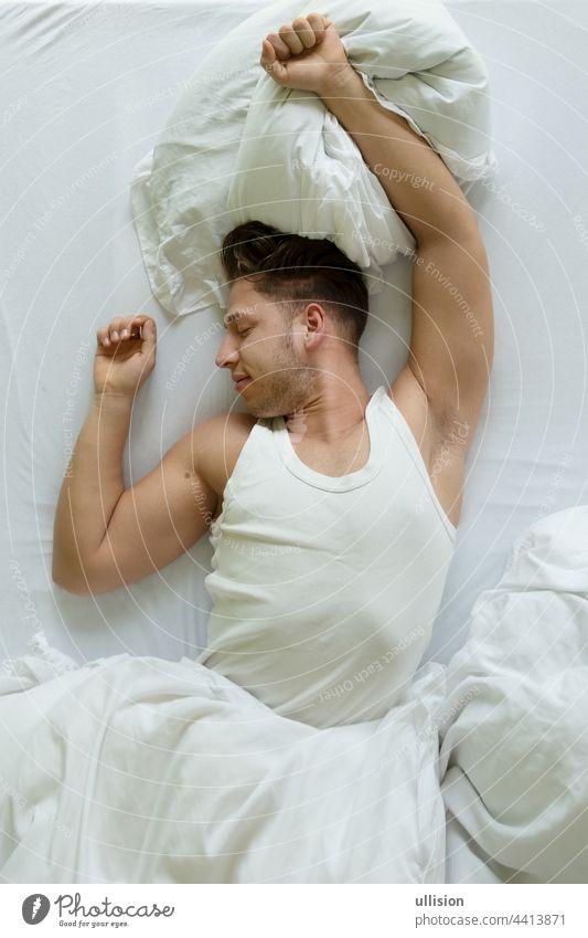 Schlafenszeit. Draufsicht auf einen muskulösen jungen Mann im Hemd, der sich morgens im Bett ausstreckt, Raum kopieren Top Ansicht Dehnungen wach Morgen