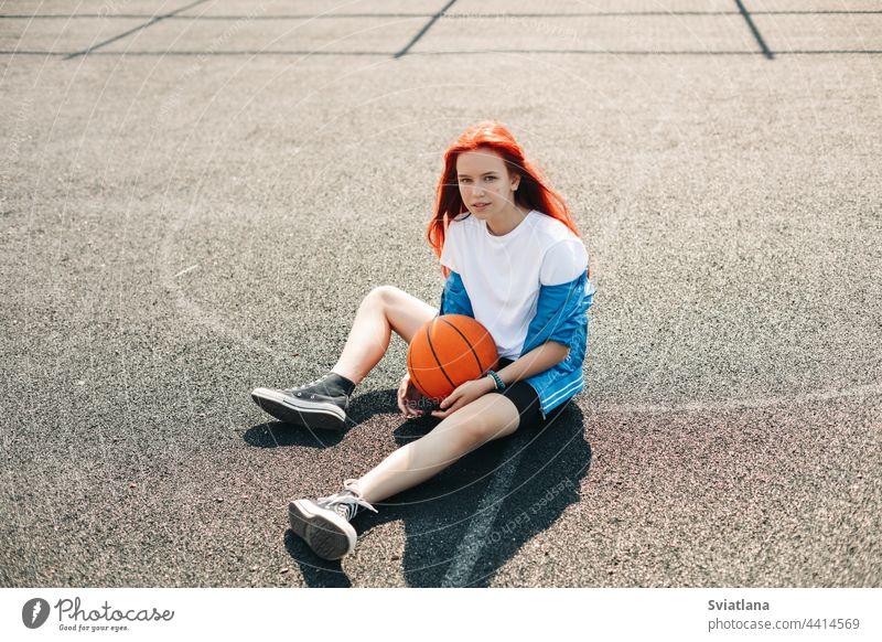 Ein charmantes junges Mädchen mit einem Basketball ruht sich nach einem Training aus. Ein Mädchen auf dem Sportplatz. Sport, Training, gesunder Lebensstil Ball