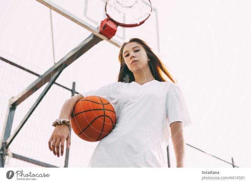 Porträt einer jungen Basketballspielerin. Schöne Teenager-Mädchen spielen Basketball. in Sportkleidung Basketball spielen Sportbekleidung Ball Korb Spieler