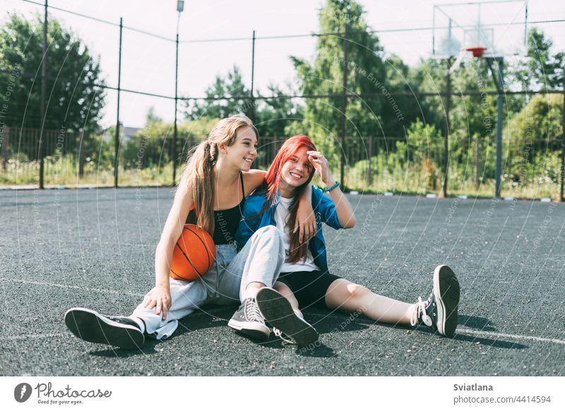 Zwei Mädchen in Sportkleidung und mit einem Basketball sitzen auf dem Spielplatz und unterhalten sich. Sport, Wettbewerb, Freundschaft Ball Teenager Gericht