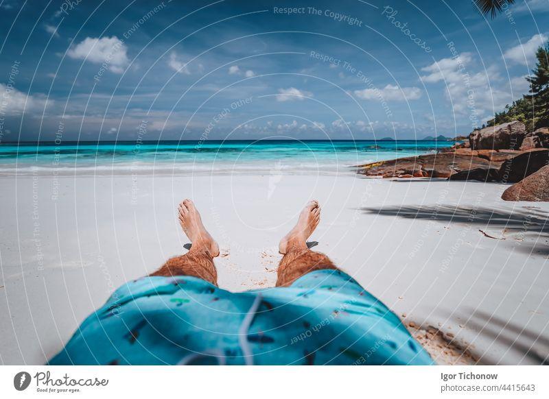 POV von männlichen tragen Badeshorts mit gebräunten Beinen auf Paradies weißen Sand tropischen exotischen Strand mit Blick auf türkisblauen Ozean. Reisen Urlaub Urlaub Konzept