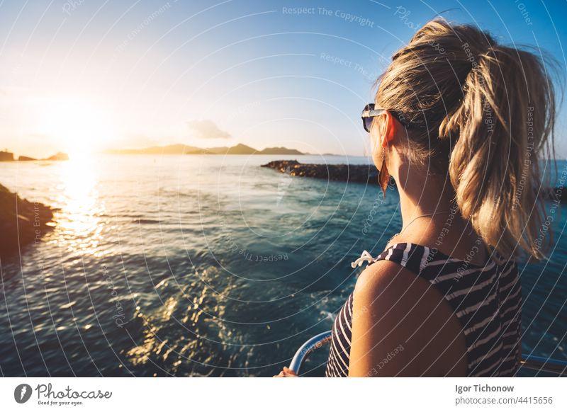 Junge erwachsene Frauen genießen den Sonnenuntergang über dem Meer von der Fähre aus, Seychellen Insel, La Digue golden Silhouette Mädchen digue jung reisen
