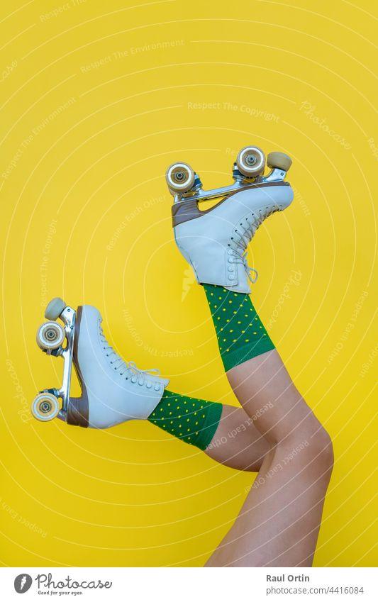 Frau mit Vintage-Quad-Rollschuhen und grünen Socken auf gelbem Hintergrund Rolle Schlittschuhe Spaß Klinge Beine Sport Sommer altehrwürdig vierfach Lifestyle