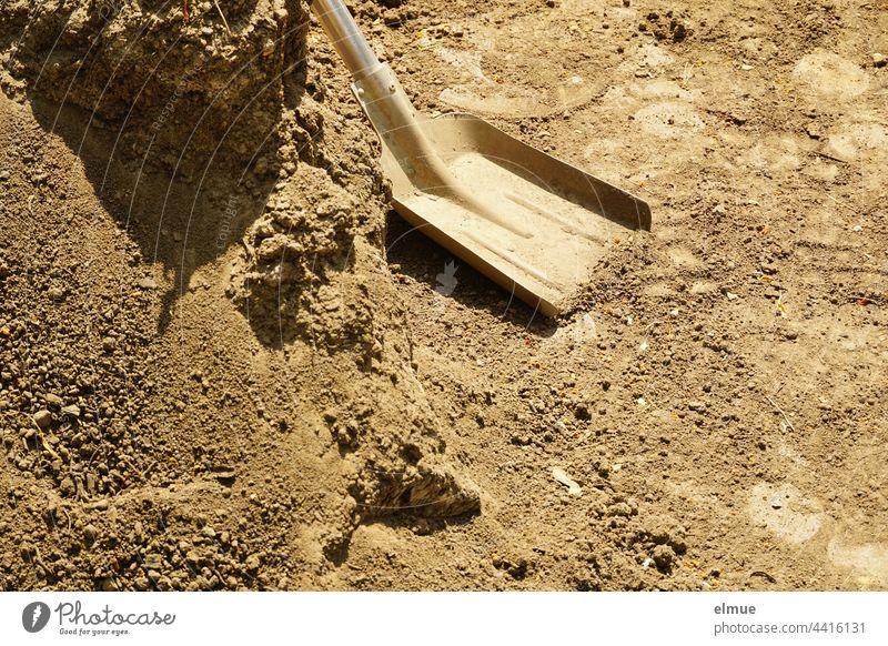 Schaufelblatt mit Metallstiel und ein Berg Kies / Werkzeug / Bauarbeiten Stiel Schaufelstiel Fußabdruck schaufeln Handarbeit bauen Handwerk