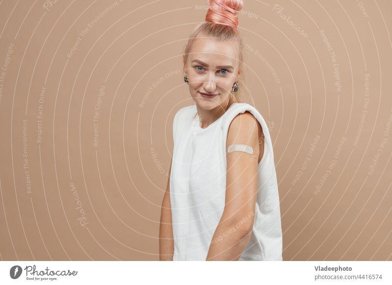 Junge Hipster-Frau mit Pflaster nach Coronavirus Covid-19-Impfung. Covid Impfung Konzept, einfarbigen Hintergrund COVID Impfstoff Einspritzung Arme jung