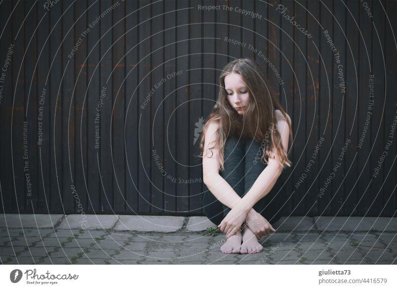 Porträt eines Teenager Mädchens, draussen auf dem Boden sitzend, allein, traurig, hoffnungslos Liebeskummer Traurigkeit Sehnsucht Trauer Enttäuschung Einsamkeit