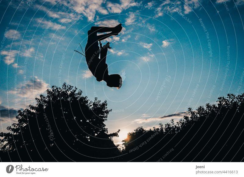 Sprung in den Sonnenuntergang Bewegung Salto schwungvoll Sonnenuntergangshimmel Schwung Dynamisch fliegen schweben Himmel springen blau Freude Freiheit Sport