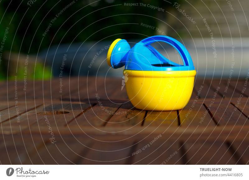 Bunte Gießkanne. Wartet auf dem Gartentisch. Auf Kinderhände. Holz Kindergießkanne bunt blaugelb Plastik Kunststoff Kinderspielzeug nützlich