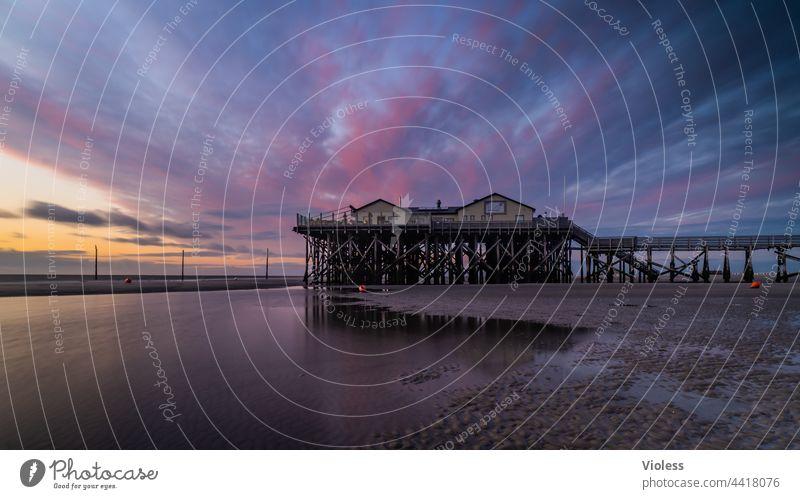 St. Peter Ording zum Sonnenuntergang Strand Nordsee Stelzenhaus Stelzenbauten Wolken dramatisch Spiegelung Küste Urlaub Reisen Abendrot