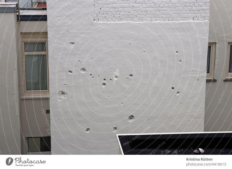 kriegsspuren an der hauswand einschüsse einschusslöcher einschläge mauer fassade hinterhof gebäude beschädigungen beschädigt kriegsschäden