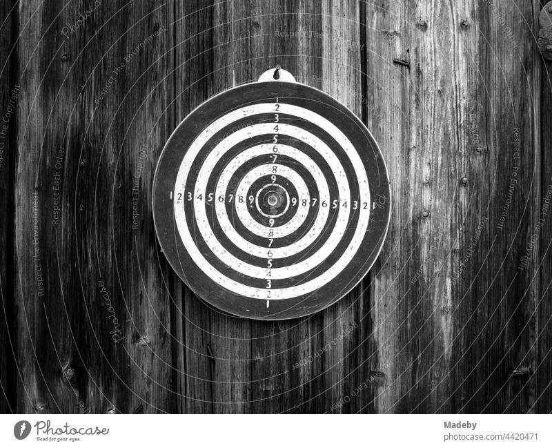 Kreisrunde alte Dartscheibe an einer Scheunenwand aus rustikalem Holz auf einem Bauernhof in Rudersau bei Rottenbuch im Kreis Weiheim-Schongau in Oberbayern, fotografiert in klassischem Schwarzweiß