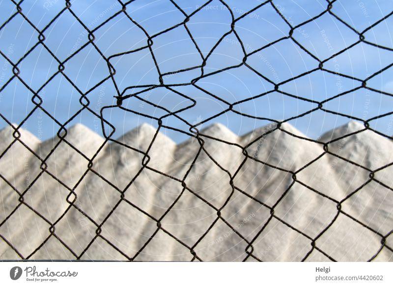Salzberge in einer Salzgewinnungsanlage hinterm Zaun Salzkristalle Trocknung aufgetürmt Lagerung Meersalz Ses Salines Mallorca menschenleer Farbfoto