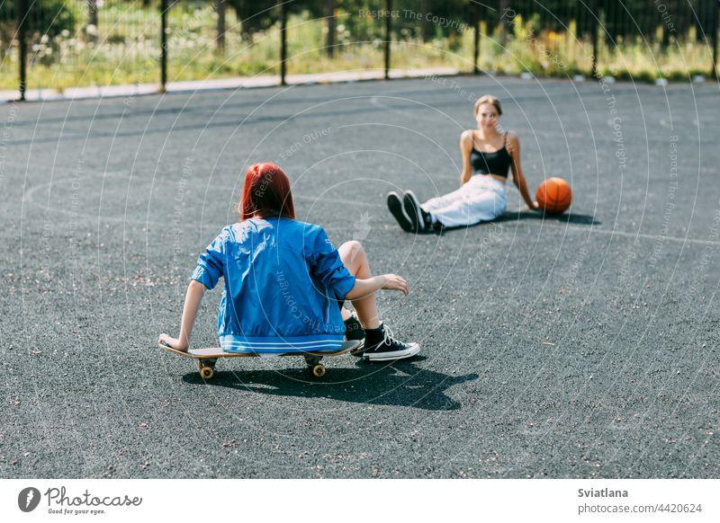 Ein junges Mädchen sitzt auf einem Skateboard im Freien auf einem Basketballplatz mit ihrem Freund, der Basketball spielt Skateboarderin Sport Skateboarding