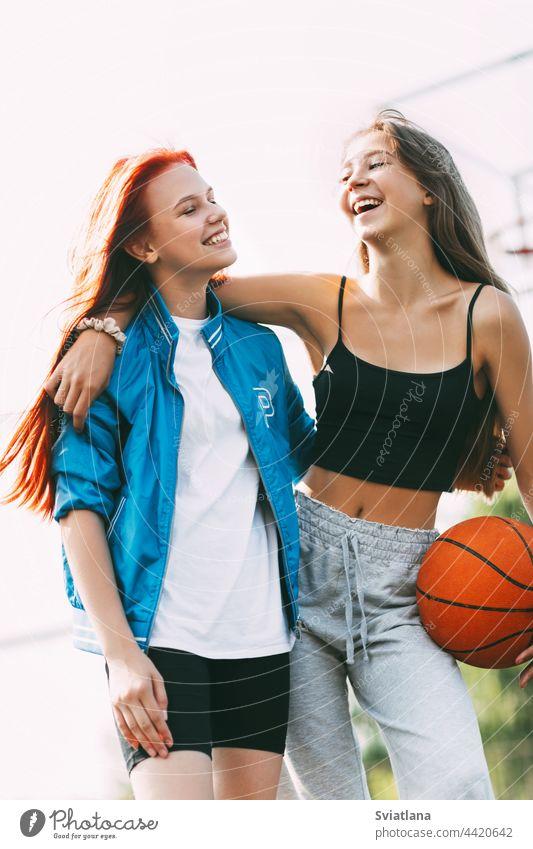 Zwei lustige Mädchen mit einem Basketball umarmen sich nach einem Spiel oder Training. Das Konzept von Sport und Freundschaft Gericht Ball Beteiligung