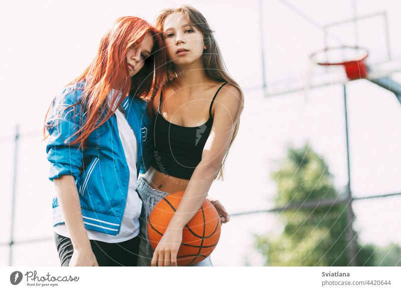 Porträt von zwei charmanten Mädchen mit einem Basketball auf dem Sportplatz. Freundschaft, beste Freunde, Sport Gericht Ball Beteiligung Basketballplatz