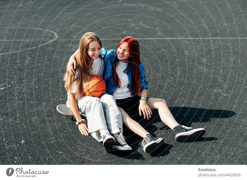 Ein paar Teenager-Mädchen entspannen sich nach einem Spiel auf einem Sportplatz mit Basketball-Lifestyle und unterhalten sich. Das Konzept des Sports und eines gesunden Lebensstils