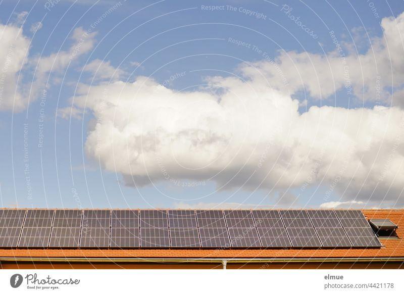 Auf dem roten Ziegeldach, neben einem Dachfenster wurden Sonnenkollektoren installiert / Dekowolken / Ökostrom / Photovoltaikanlage Energiewende Klimawandel