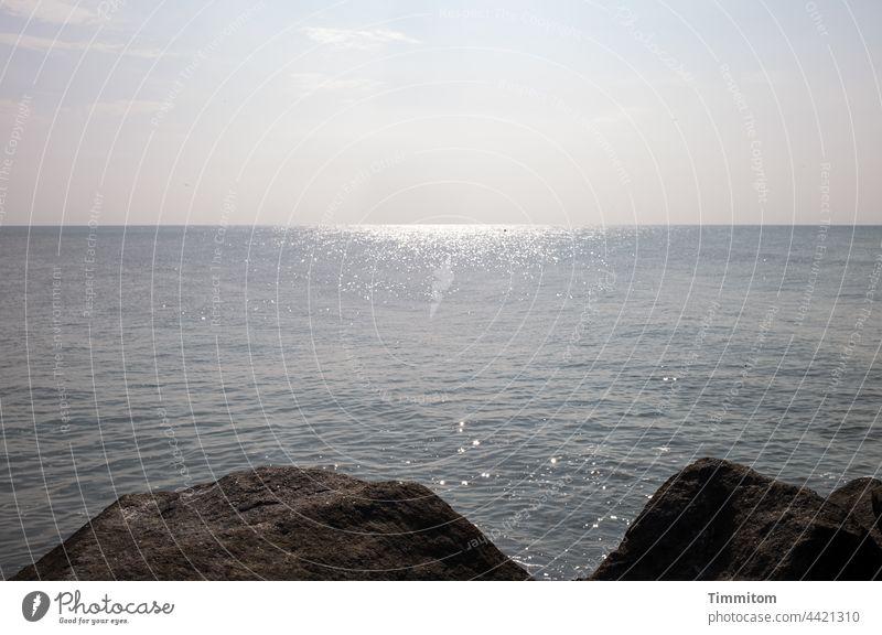 Steine einer Mole, glänzende Nordsee und sanfter Himmel Befestigung Damm Wasser ruhig Horizont Licht Meer Außenaufnahme Menschenleer Ferien & Urlaub & Reisen