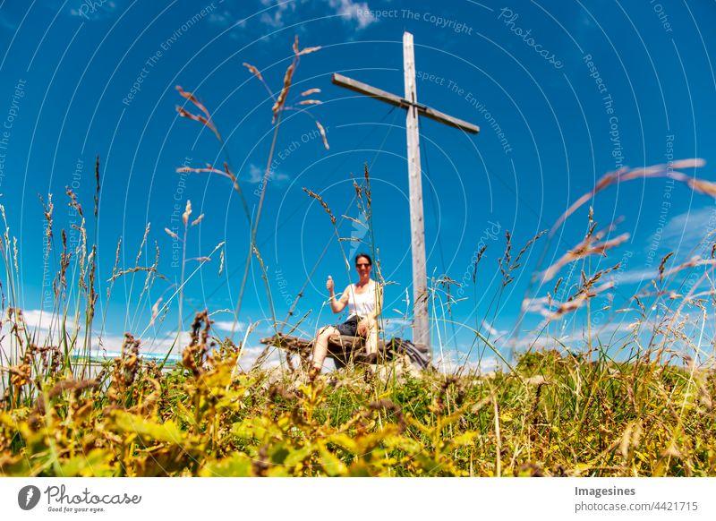 Verschwommen. Gipfelkreuz auf dem Gipfel des Berges in den bayerischen Alpen mit einem Bergsteiger, der die Daumen hochhebt. Angekommen, Siegerpose oben an einem Bergkreuz. Fokus auf Gras.