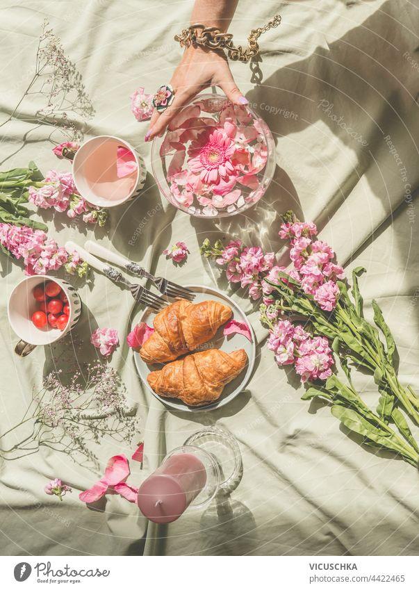 Ästhetisches Picknick am Sonnentag mit Croissants, Tee, Blumenstrauß aus rosa Blüten und Kerzen. Frauenhand hält Glasvase mit schwimmenden Blütenblättern. Ansicht von oben