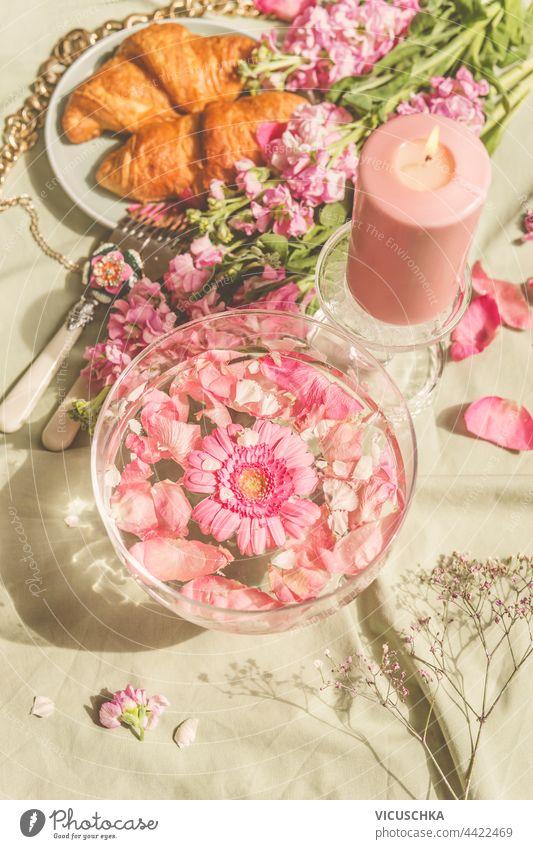 Glaswasserschale mit rosa Blumen auf Picknickdecke mit Croissants und Kerzen. Sonniger Tag. Ästhetisches Picknick-Konzept Wasser Schalen & Schüsseln Decke