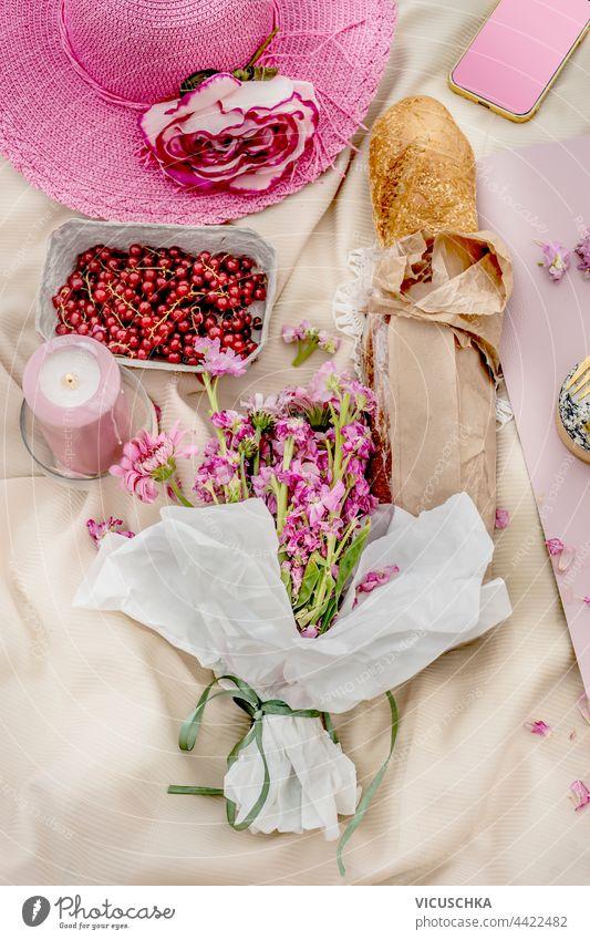 Rosa Hut mit Baguette, Blumenstrauß und Obst auf Picknickdecke. Ansicht von oben. Draußen. rosa Haufen Früchte Decke Draufsicht im Freien außerhalb Tischwäsche