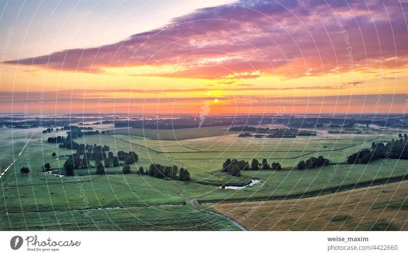 Dramatischer Sommer-Sonnenaufgang. Panorama neblige Landschaft. Nebliger Morgen am Fluss Luftaufnahme. Grüne Felder und Wiesen Natur Himmel Sonnenlicht