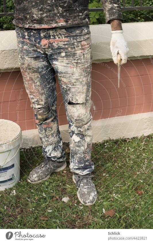 Stehender Maler vor frisch angestrichener Mauer Hose Schuhe Pulli Handschuh und Werkzeug mit reichlich Farbflecken Wandfarbe Unterkörper Beine stehen Farbeimer