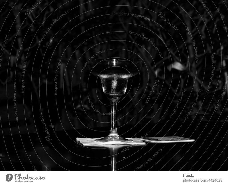 Einsames Cocktailglas Glas Restaurant leer Gastronomie Biergarten Tisch Serviette Bierdeckel Busch Blatt Abend dunkel