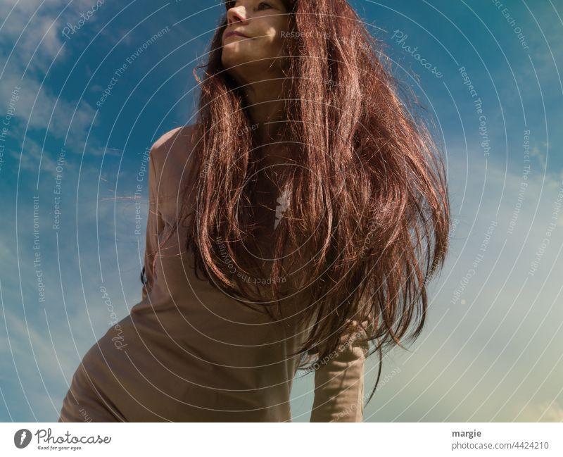 Eine Frau mit langen Haaren schaut in den Himmel Junge Frau feminin Mensch Außenaufnahme Wolken Porträt Haare & Frisuren Erwachsene Gesicht Farbfoto