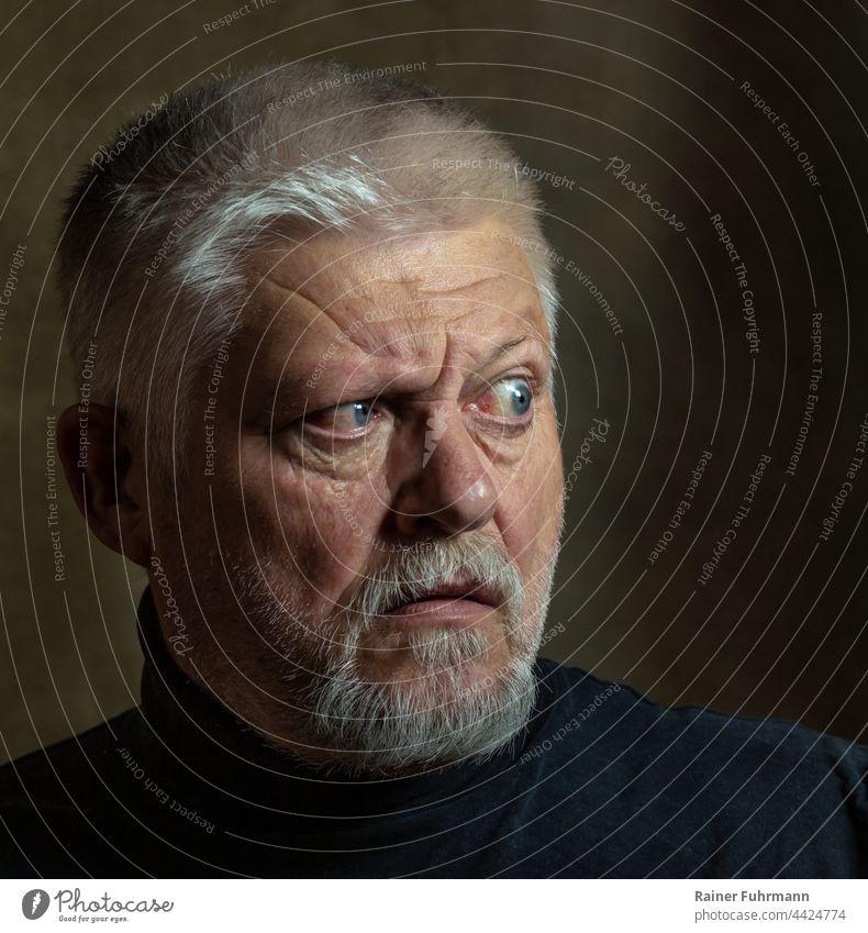 Ein älterer Mann mit Bart blickt angespannt zur Seite. Porträt Mensch Gesicht dunkel Blick Mimik Gesichtsausdruck Rembrandtlicht ernst maskulin Angst Anspannung