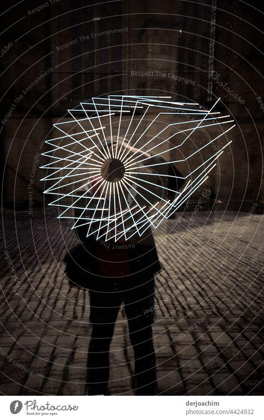 Scheibenkunst einmal ganz anders.  Die Schaufenster Scheibe zeigt Risse. Im Abendlicht steht der Fotograf mit Tasche auf der gepflasterten Straße vor der gerissenen Scheibe.