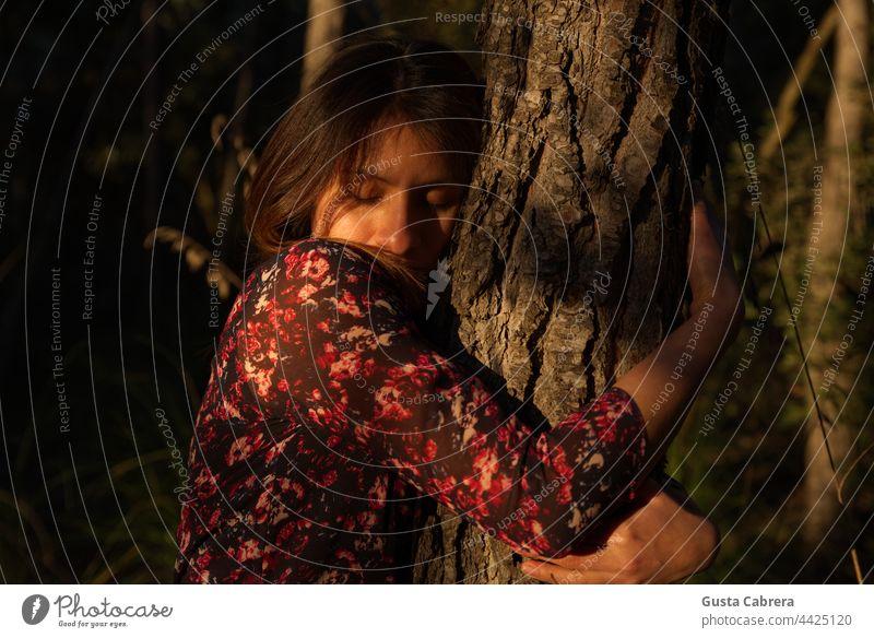 Frau in rotem Blumenkleid umarmt einen Baum. Liebkosen Baumstamm Außenaufnahme Farbfoto Kofferraum Natur Wald Gefühl Sonnenuntergang natürlich Kontakt