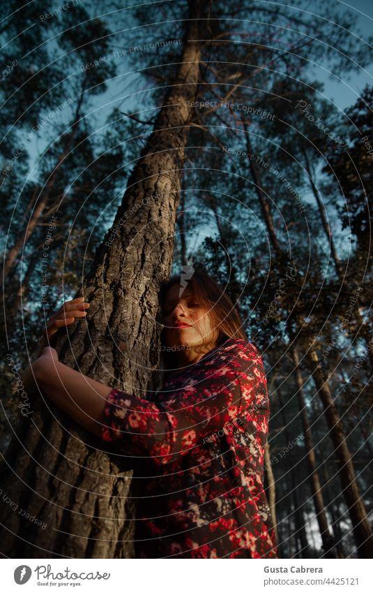 Frau in rotem Blumenkleid umarmt einen Baum. Junge Frau Liebkosen Bäume Menschen feliz Gefühl Erholung sich[Akk] entspannen im Freien Natur