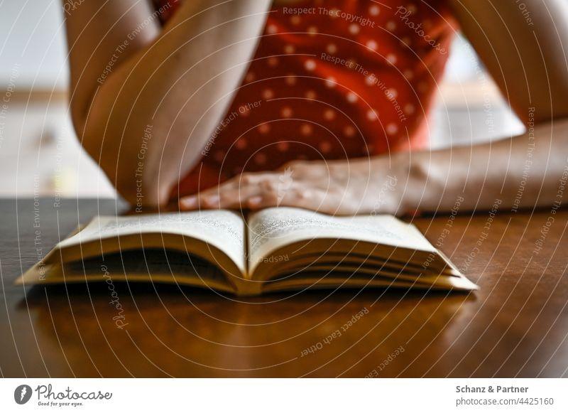 Frau liest ein Buch am Tisch lesen Bücher Hand Hände Seiten blättern vertieft Literatur Buchhandlung Bücherei Lesestoff Roman Studium Wissen lernen Bildung