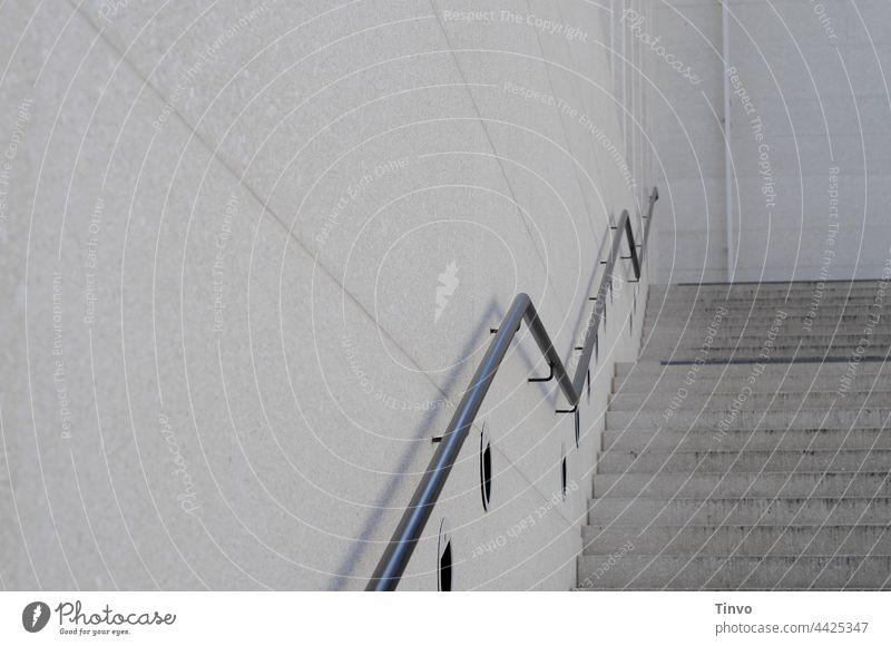 schlichter Treppenaufgang mit Geländer im Zickzack Treppengeländer Handlauf Stufen aus Beton schlichter Hintergrund Architektur Wand Außenaufnahme aufwärts