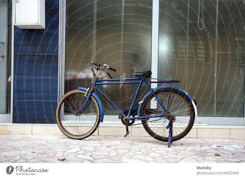 Altes blaues Fahrrad vor blauem Hauseingang mit viel Glas in Adapazari in der Provinz Sakarya in der Türkei Rad Herrenrad Tourenrad Stadtrad Radfahrer Radfahren