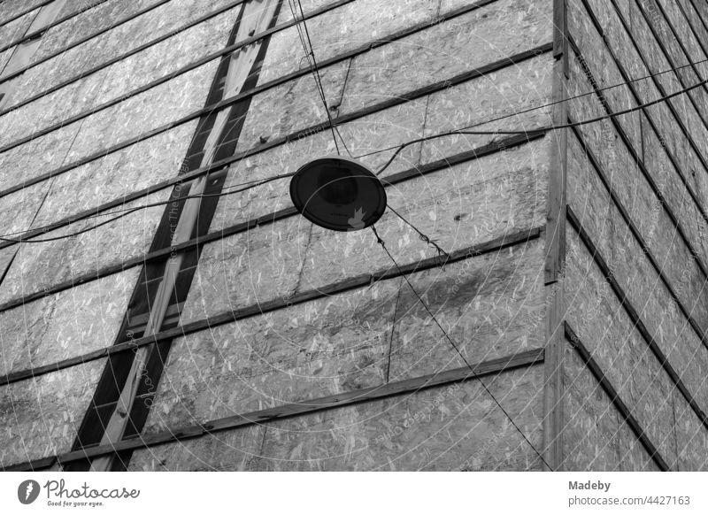 Straßenbeleuchtung an alten Stromkabeln vor einer Fassadenverkleidung mit Spanholzplatten im Galataviertel im Stadtteil Beyoğlu in Istanbul am Bosporus in der Türkei, fotografiert in neorealistischem Schwarzweiß