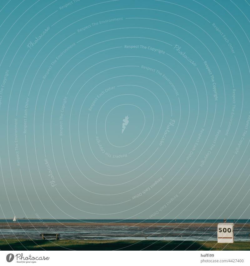Strandkorb 500, Bank und Segelboot bei Ebbe und wolkenlosem Himmel  an der Nordseeküste Spätsommer Wolkenloser Himmel spätsommerlich Sitzbank Küste Idylle